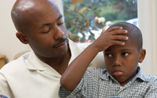 African American boy with holding his forehead while sitting on his father