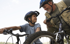 Grandson and Grandfather on bikes with helmets