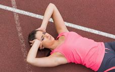 Female lying on track holding her head